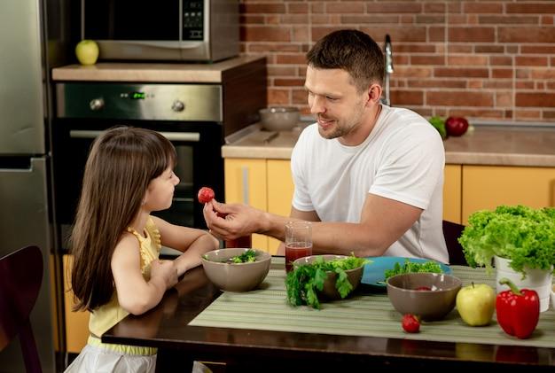 Pai alegre e filha tomando café da manhã juntos na cozinha