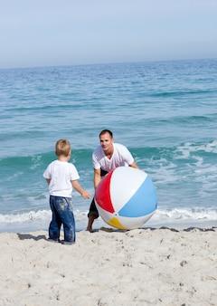 Pai alegre e seu filho brincando com uma bola