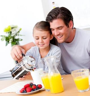 Pai alegre e sua filha tomando café da manhã juntos