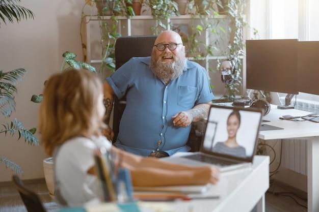 Pai alegre olha para uma menina estudando à distância com o laptop na sala de luz