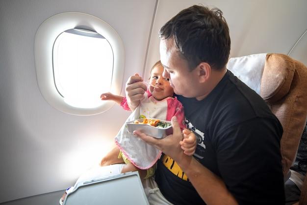 Pai alimenta a criança pequena no avião com refeições especiais.
