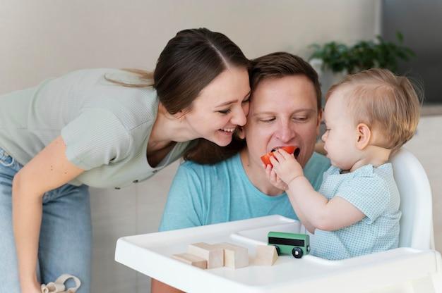 Pai alimentando criança tiro médio