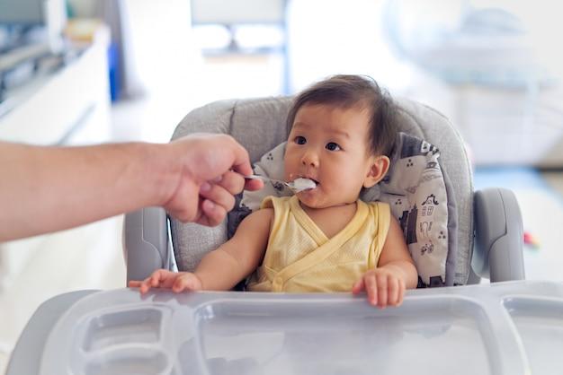 Pai alimentando mingau para o filho no assento de alimentação do bebê.