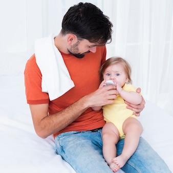 Pai alimentando o bebê na cama