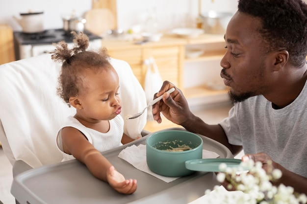 Pai alimentando sua filhinha na cozinha