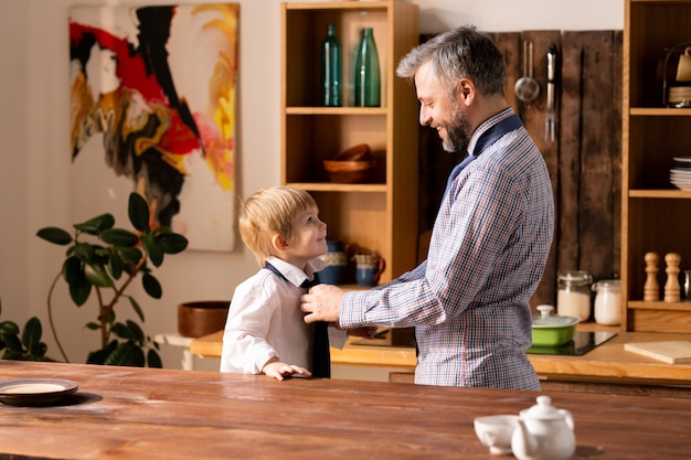 Pai amarrar gravata para filho pequeno