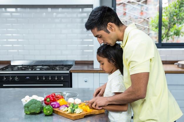 Pai amável ajudando sua filha a cortar vegetais