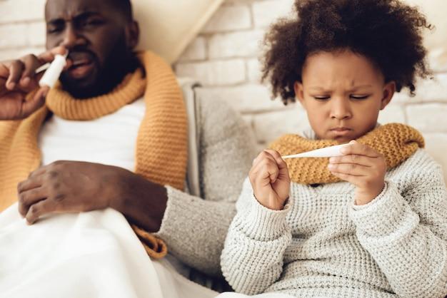 Pai americano africano doente e filha sentada na cama