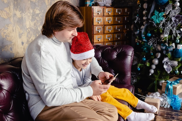 Pai amoroso animado segurar tablet sentar no sofá com desenho animado relógio filho pré-escolar bonito juntos sobre fundo de natal. pai feliz sorridente e filho pequeno relaxam no sofá em casa, jogam no teclado.