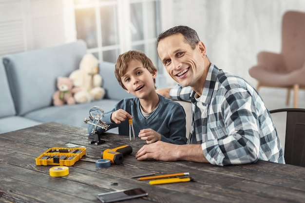 Pai amoroso. homem atraente e alegre de cabelos escuros mostrando instrumentos para seu filho enquanto está sentado à mesa e seu filho segurando uma bússola e sorrindo