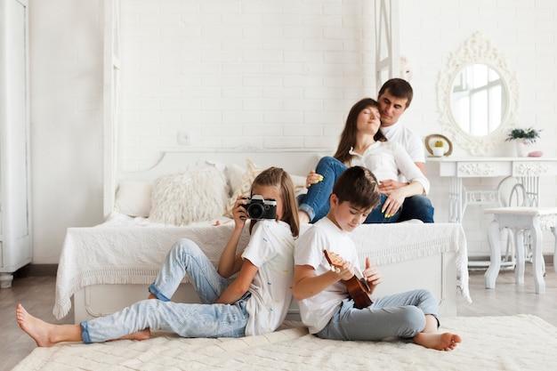 Pai amoroso sentado na cama e sua filha segurando a câmera e filho tocando cavaquinho