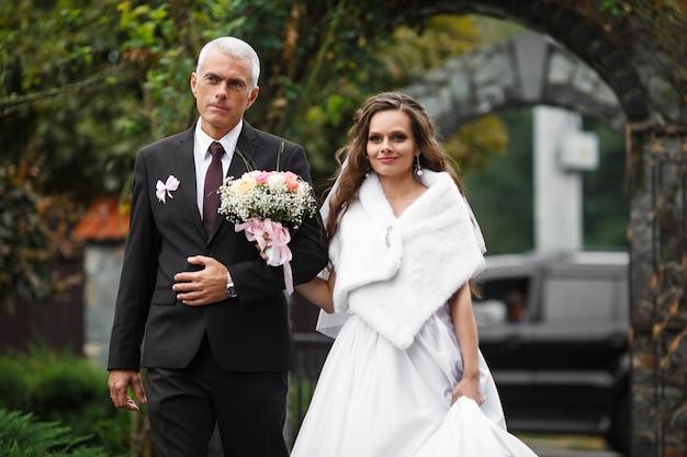 Pai anda com uma noiva ao longo do quintal