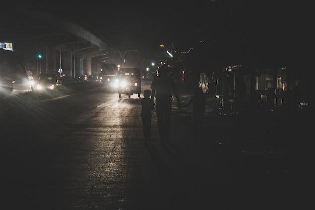 Pai andando com seus dois filhos à noite na cidade
