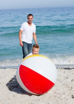 Pai animado e seu filho brincando com uma bola