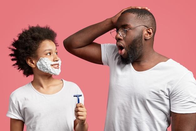 Pai apavorado olha para o filho pequeno que imita o pai, quer se barbear ainda jovem
