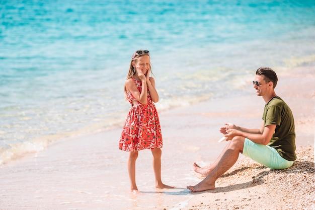 Pai, aplicar creme de proteção solar para sua filha na praia tropical