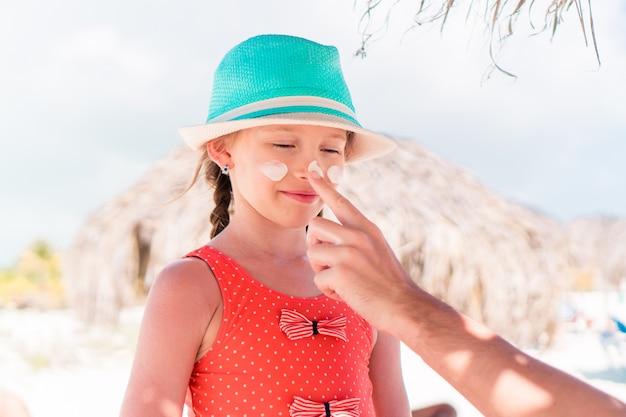 Pai, aplicar protetor solar no nariz da filha.