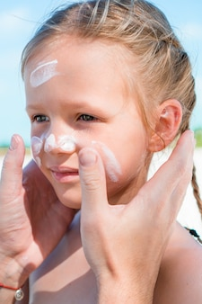 Pai aplicar protetor solar para sua filha