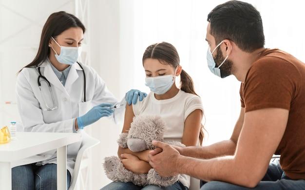 Pai apoiando a filha que está sendo vacinada