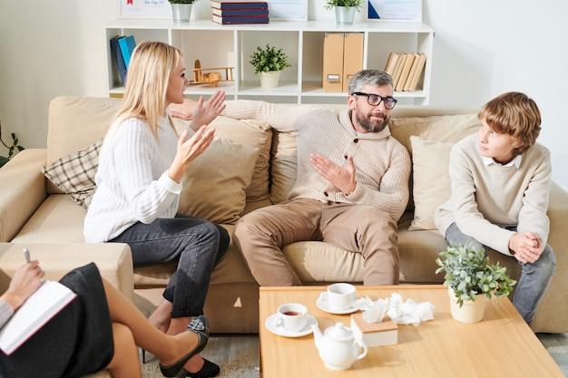 Pai apontando emocional mãe para filho na sessão de terapia
