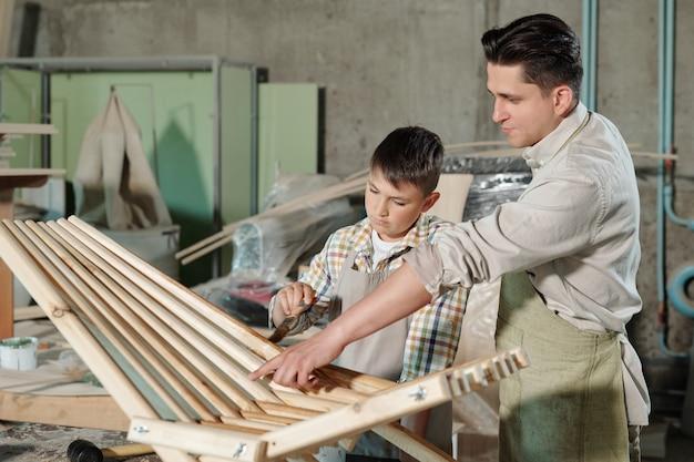 Pai apontando o filho para lugares não envernizados da cadeira de madeira para o filho enquanto eles fazem móveis na oficina