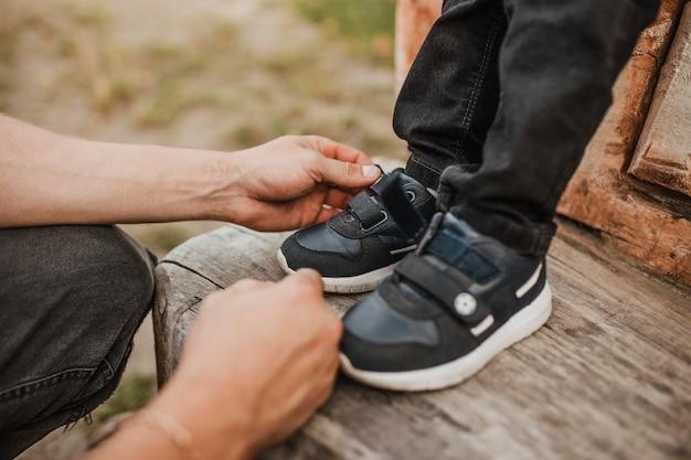 Pai arrumando os sapatos do filho