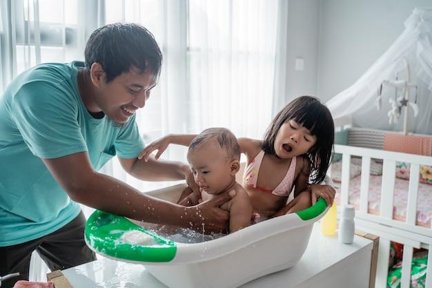Pai asiático dando banho para sua criança bebê
