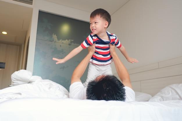 Pai asiático, deitado na cama, brincando com o avião de atuação da criança menino bonitinho da criança, sendo um pai bom e forte, conceito de feliz dia dos pais