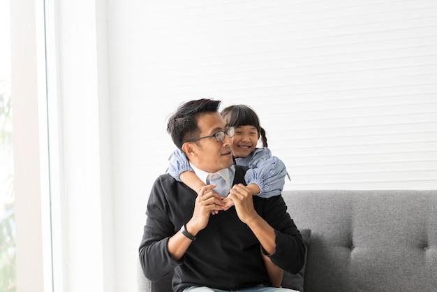 Pai asiático e filha que jogam e que abraçam junto na sala de visitas em casa.