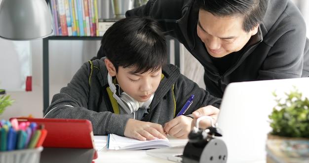 Pai asiático e filho que fazem trabalhos de casa em casa.