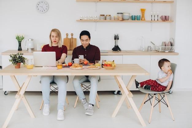 Pai asiático e mãe europeia trabalham com seus aparelhos, e o filho toma café da manhã sozinho. problemas tecnológicos modernos.
