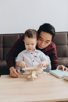 Pai asiático e seu lindo filho brincando com um avião de madeira em uma sala iluminada