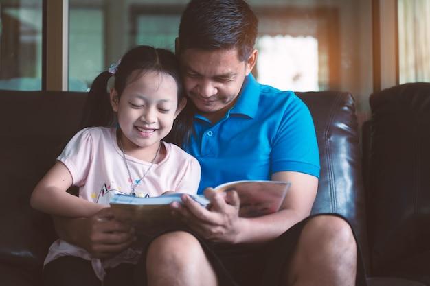 Pai asiático e sua filha lendo um livro em casa