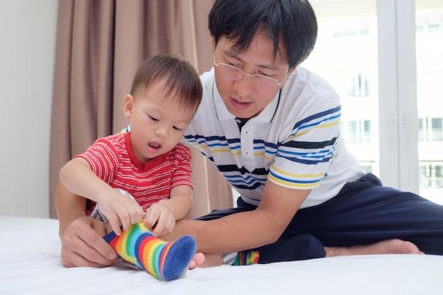 Pai asiático ensinando bonitinha asiática 2 anos de idade, criança menino, calçar as próprias meias, pai e filho sentado na cama, concentrar-se em usar meias, incentivar o conceito de habilidades de auto-ajuda em crianças
