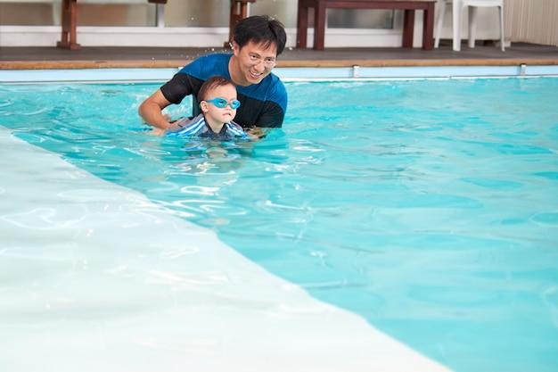 Pai asiático, filho, leva, um, lição natação, piscina interior, cute, pequeno, asiático, 2 anos velho, criança menino criança, óculos desgastando natação, aprender, nadar