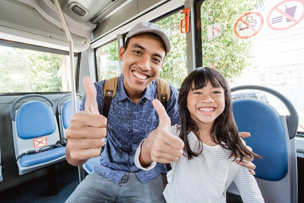 Pai asiático levando a filha para a escola de ônibus polegar para cima