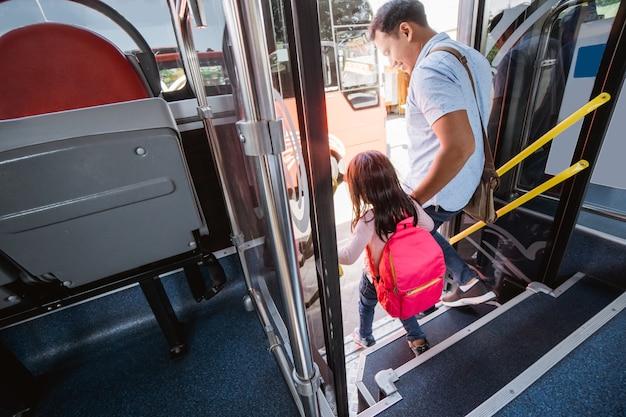 Pai asiático levando a filha para a escola em ônibus de transporte público