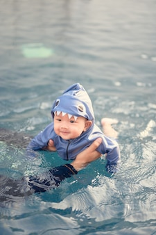 Pai asiático nadando com bebê adorável fofo na piscina