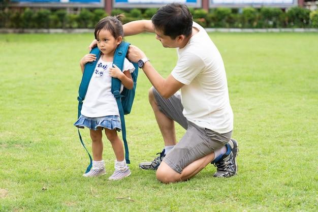 Pai asiático que ajuda a levar o saco de escola para a filha.