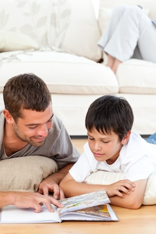 Pai atencioso, lendo um livro com seu filho deitado no chão