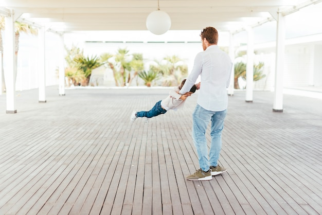 Pai, balançando, criança, por, braços, ligado, beachfront