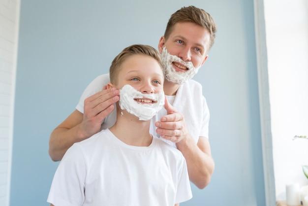 Pai barbear seu filho no banheiro