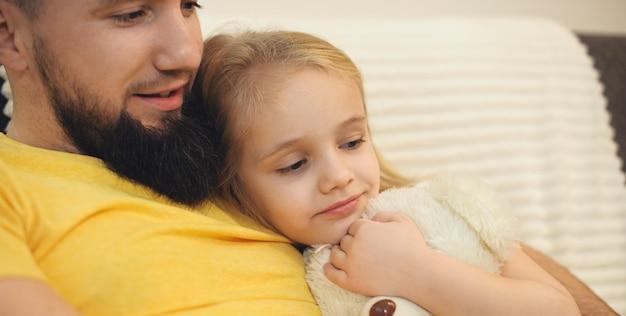 Pai barbudo e sua filha deitados na cama com um urso e assistindo a algo