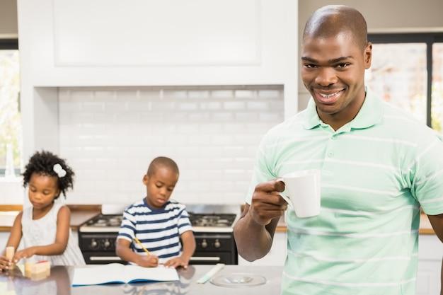 Pai bebendo bebida quente com crianças em segundo plano