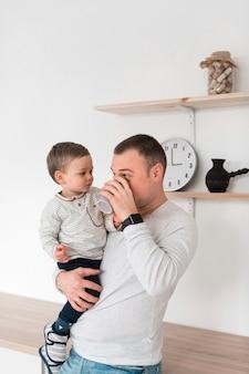 Pai bebendo da caneca, segurando o bebê