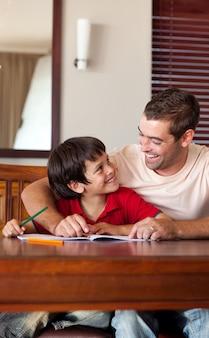 Pai bonito ajudando seu filho a fazer a lição de casa