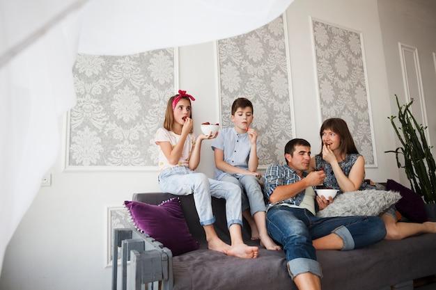 Pai bonito e seus filhos comendo morango enquanto está sentado no sofá