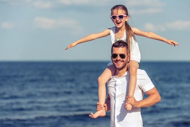 Pai bonito e sua filha pequena em óculos de sol