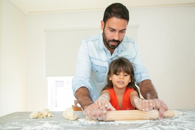 Pai bonito ensinando filha a assar.