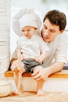 Pai bonito jovem sério morena explica ao filho pequeno, um cozinheiro, como misturar a massa com uma espátula de madeira. conceito de transferência de experiência geracional